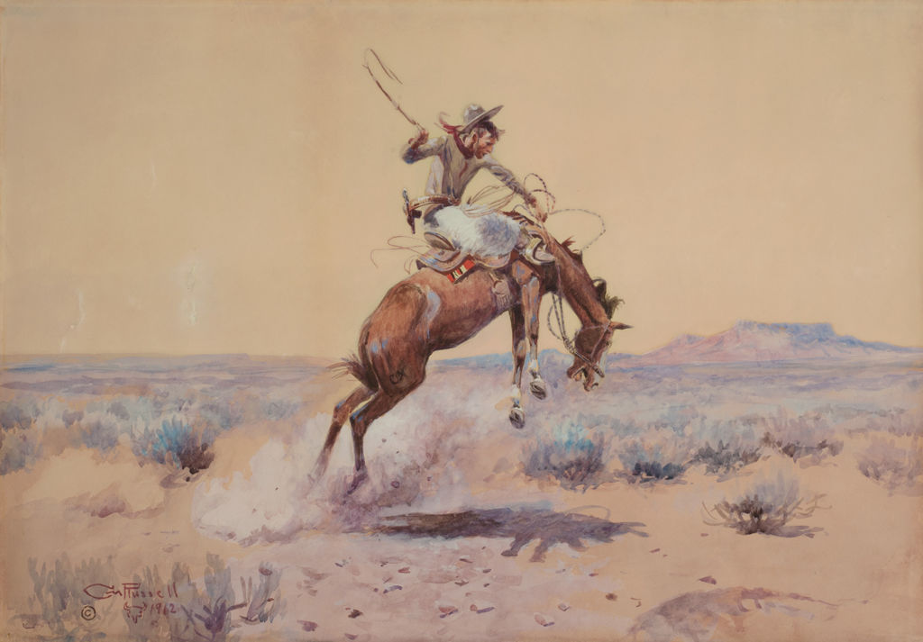 A cowboy rides a bucking horse in an open landscape.