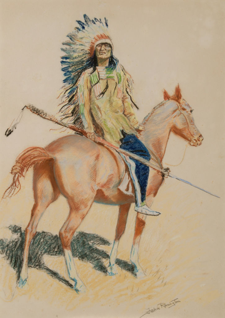 A Sioux chief in a headdress sits on a horse.