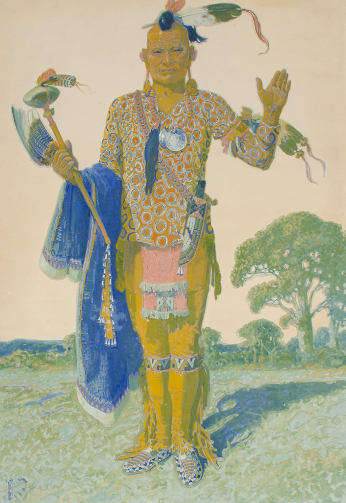 A full length portrait of a standing Apache man in tribal clothing.