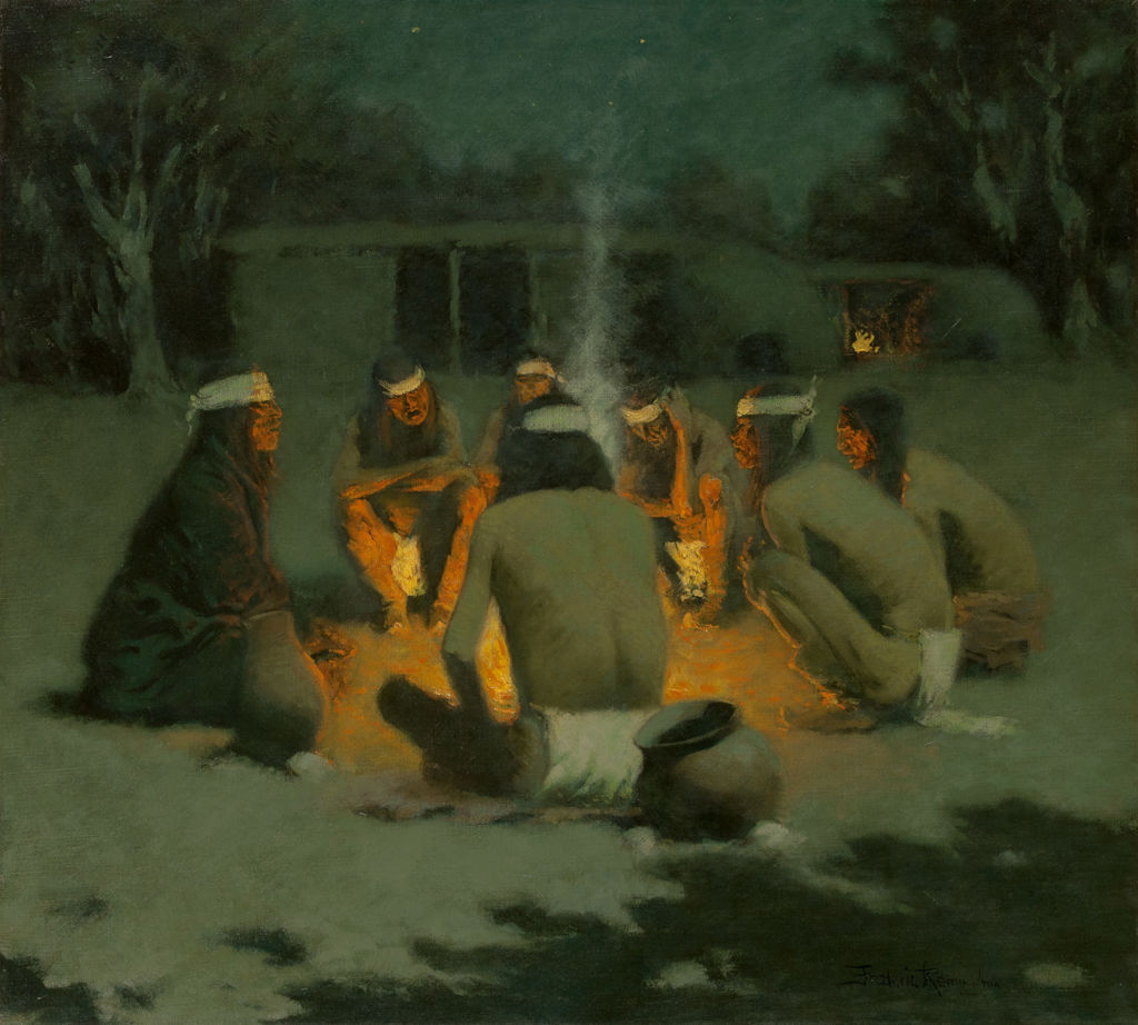 A group of Apache Indians gather closely around a campfire at night.