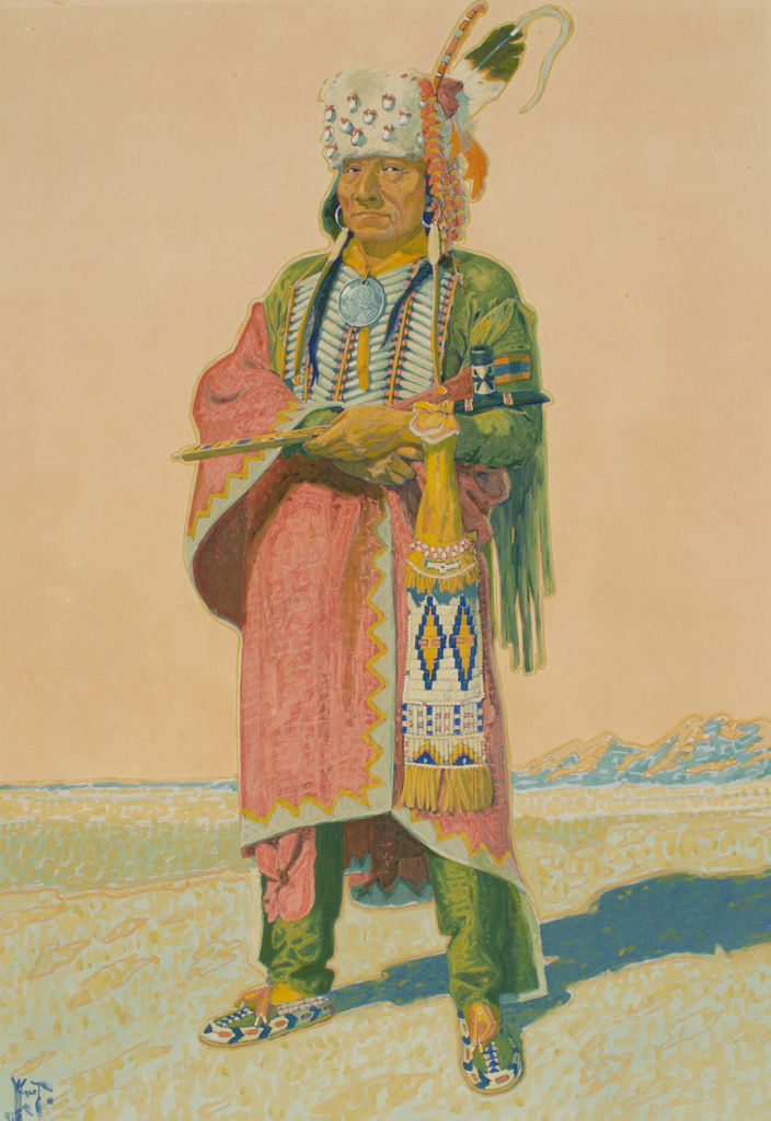 A full length portrait of an Arapaho man in tribal clothing.