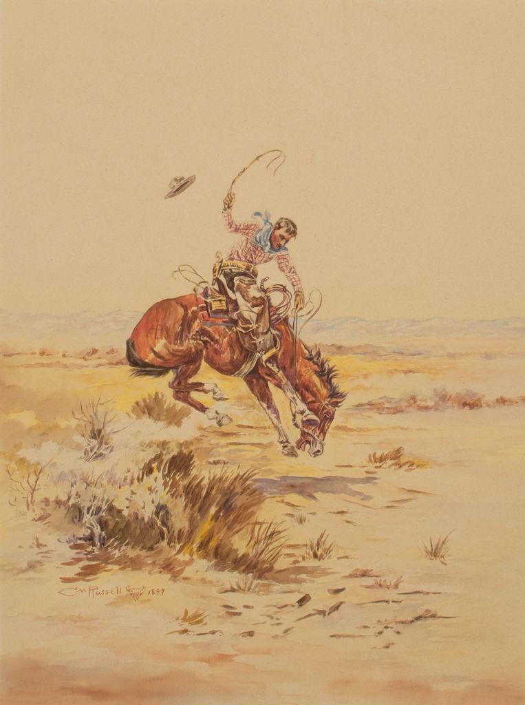 A cowboy rides a bucking horse.