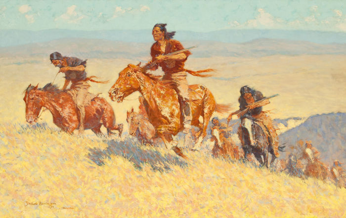 A group of indigenous American men holding rifles gallop up a hill on horseback.