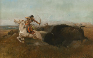 At full gallop, an indigenous American man on a white horse aims a bow and arrow at a running bison.