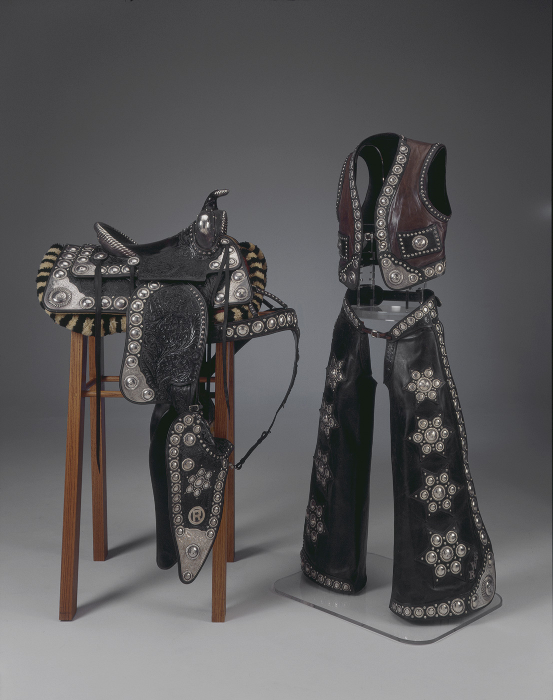 A black leather saddle decorated with sterling silver on a wooden armature next to a matching vest and chaps.