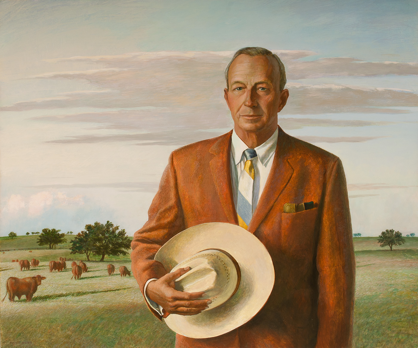 A half-length portrait of a man in a suit, holding a cowboy hat.