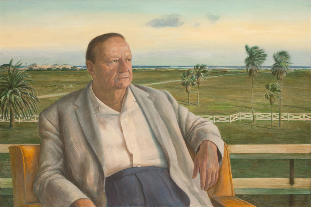 A portrait of a man seated in front of a landscape.