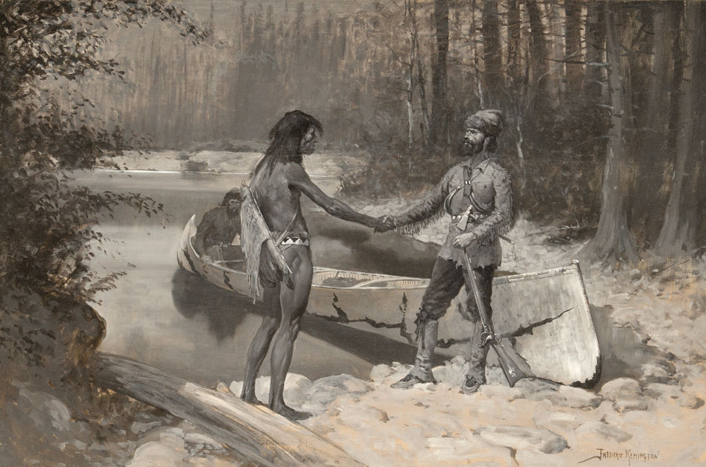 An Anglo man and indigenous American man shake hands while standing next to a canoe in a wooded embankment.