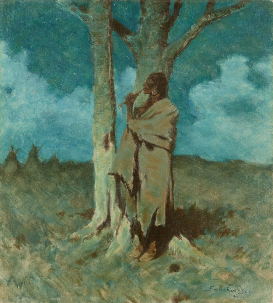 An indigenous American man stands next to a tree playing a flute at night.
