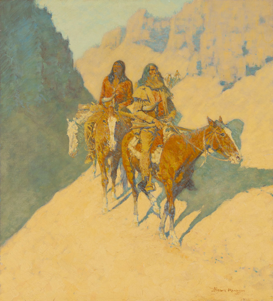 An Anglo man and an indigenous American ride horses through a shadowed canyon.