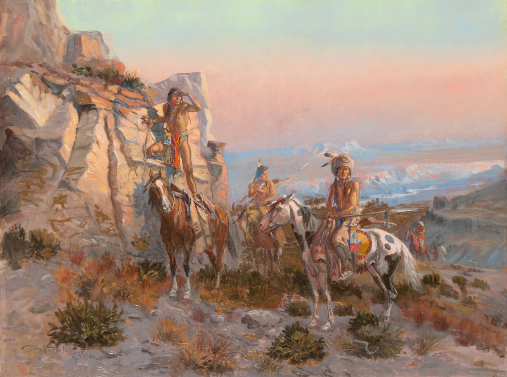 A small group of indigenous American men on horseback are stopped near a rocky outcrop looking out into the distance.